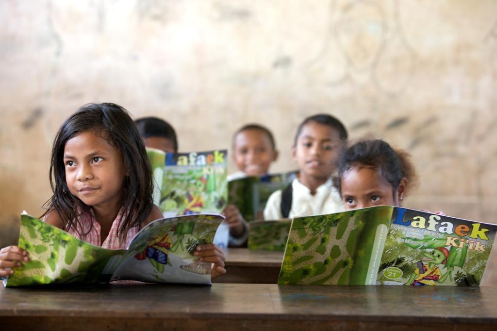 School children at Leo Hitu Primary School, read their copies of CARE Timor-Leste educatioal magazine, 'Lafaek'. Mohak sub-village, Bobonaro, East Timor. Christiani do Santos, 6 years.
